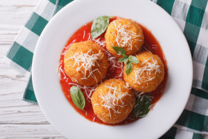 fried arancini rice balls with tomato sauce closeup. horizontal top view